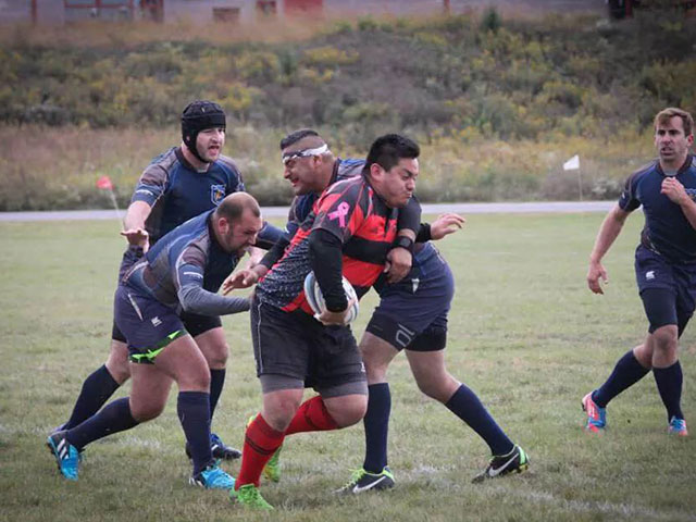 Alex running the ball up the Rugby field.