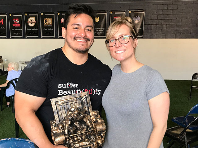 Alex and wife pose with powerlifting award